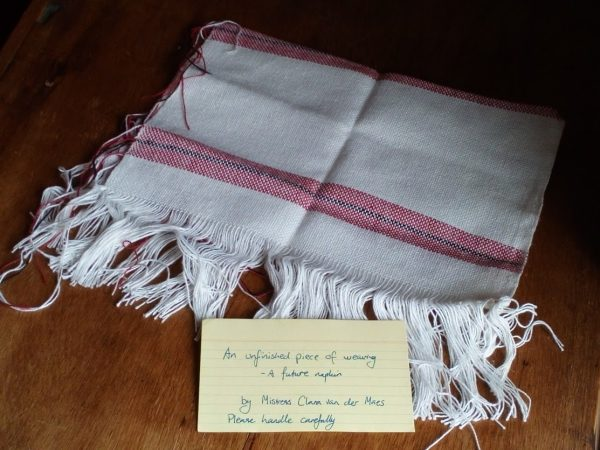 photo of a piece of weaving with a small handwritten card in front of it